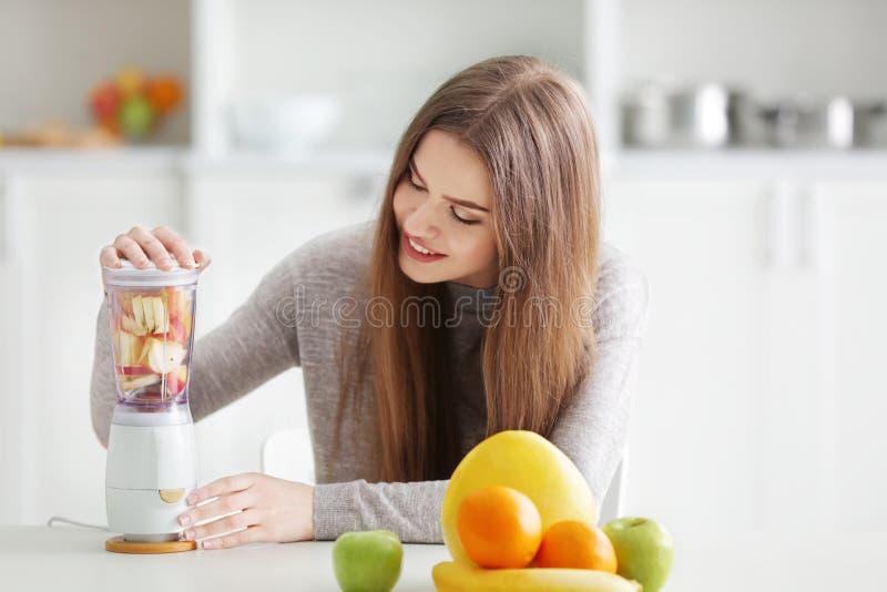 Jonge vrouw die verse smoothies in mixer voorbereiden stock afbeeldingen