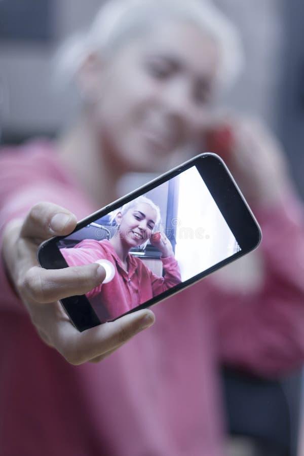 Jonge vrouw die vertoning van mobiele celtelefoon tonen die een selfie nemen stock foto