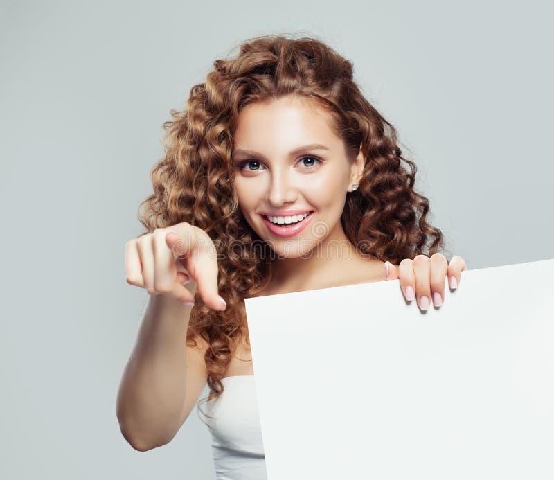 Jonge vrouw die vinger richten en witte lege kartonachtergrond met exemplaarruimte houden voor reclame marketing stock afbeeldingen