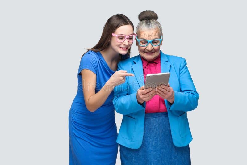 Jonge vrouw die vinger richten op tablet in handen oude vrouw royalty-vrije stock afbeelding