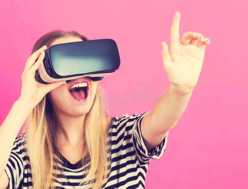 Jonge vrouw die virtuele werkelijkheidshoofdtelefoon met behulp van stock foto's