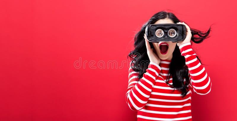 Jonge vrouw die virtuele werkelijkheidshoofdtelefoon met behulp van