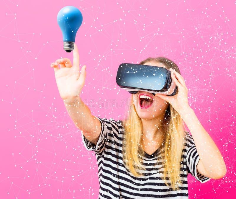Jonge vrouw die virtuele werkelijkheidshoofdtelefoon met lightbulb met behulp van stock afbeelding