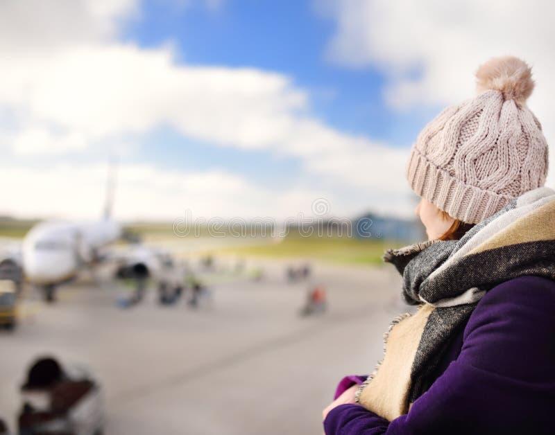 Jonge vrouw die vliegtuigen in Internationale luchthaven bekijken royalty-vrije stock foto