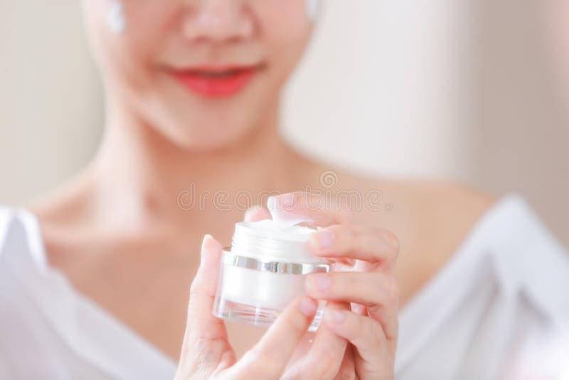 Jonge vrouw die vochtinbrengende crème op haar gezicht toepast en kruik houdt van royalty-vrije stock foto