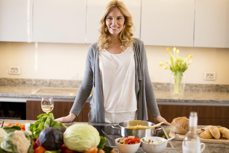 Jonge vrouw die voedsel in moderne keuken voorbereiden stock afbeelding