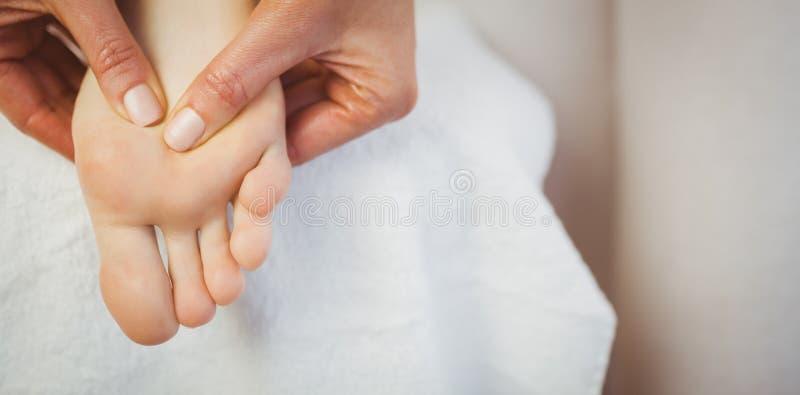 Jonge vrouw die voetmassage krijgen stock afbeelding