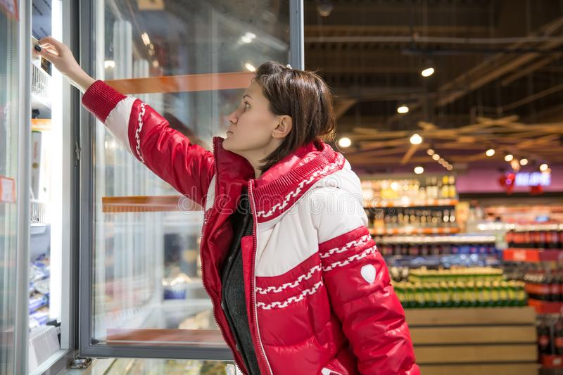 Jonge vrouw die voor gesmolten producten in een kruidenierswinkelopslag winkelen Zelfbediening stock afbeelding