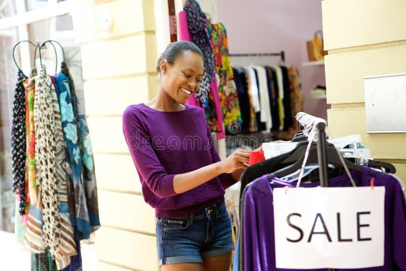 Jonge vrouw die voor kleren bij opslag winkelen royalty-vrije stock afbeelding