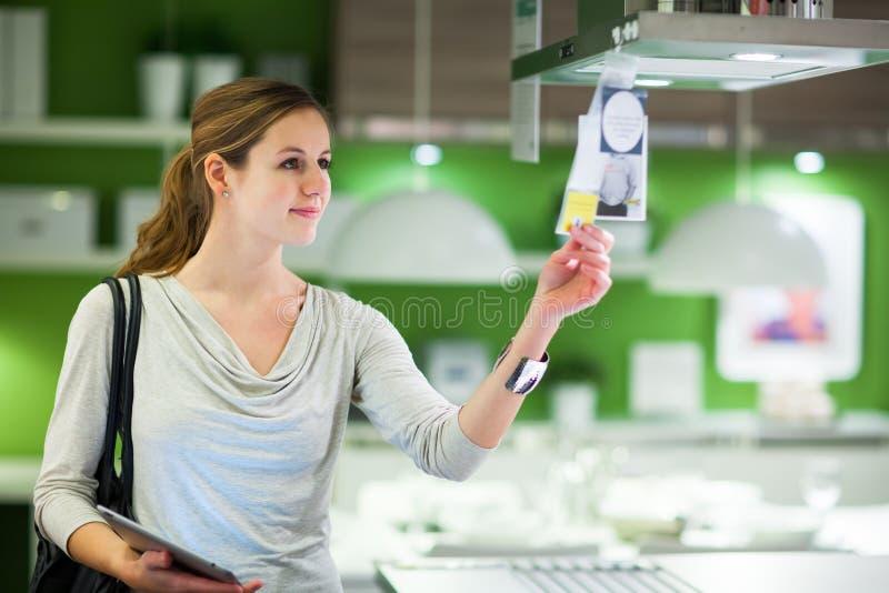 Jonge vrouw die voor meubilair in een meubilairopslag winkelen stock foto's