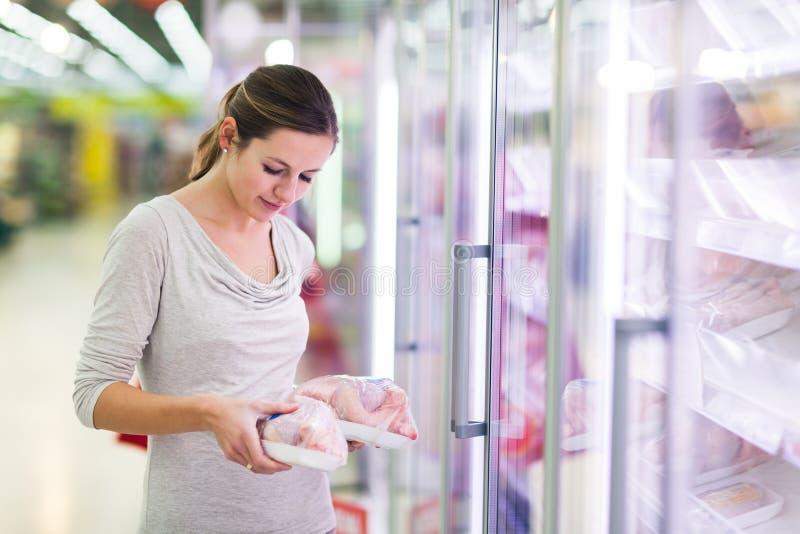 Jonge vrouw die voor vlees in een kruidenierswinkelopslag winkelen stock fotografie