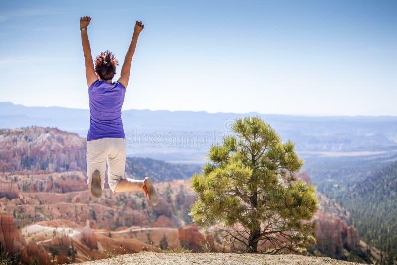 Jonge vrouw die vreugdevol in Bryce Canyon Park springen royalty-vrije stock afbeelding
