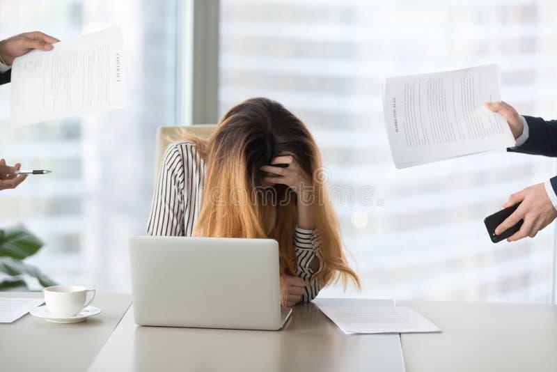 Jonge vrouw die wanhopig bij werk voelen die, van het werk wordt het vermoeid stock afbeeldingen