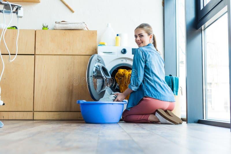 jonge vrouw die wasserij van wasmachine en het glimlachen nemen stock afbeelding