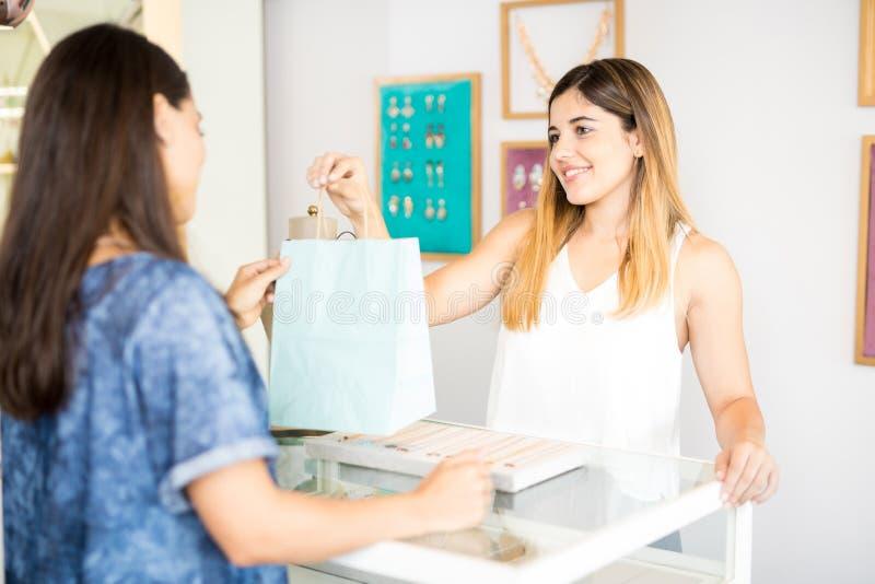 Jonge vrouw die wat juwelen verkopen stock fotografie