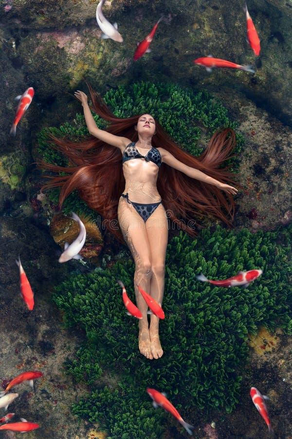 Jonge vrouw die in water drijft stock foto's