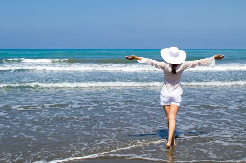 Jonge vrouw die weg het overzees op het strand bekijken royalty-vrije stock fotografie