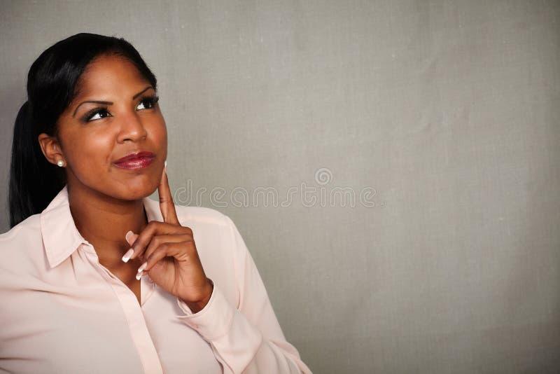 Jonge vrouw die weg met een het denken gebaar kijken stock foto's