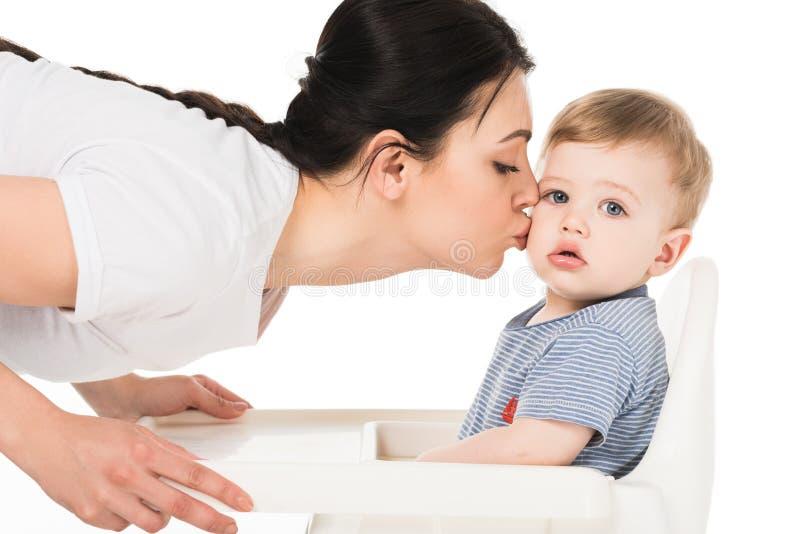 jonge vrouw die weinig zoon in highchair kussen stock afbeelding