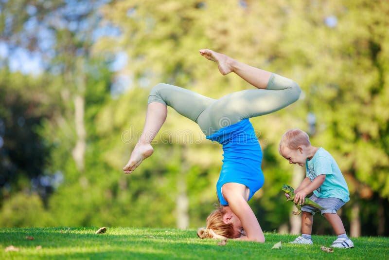 Jonge vrouw die, weinig zoon die naast haar spelen in openlucht uitwerken royalty-vrije stock foto's