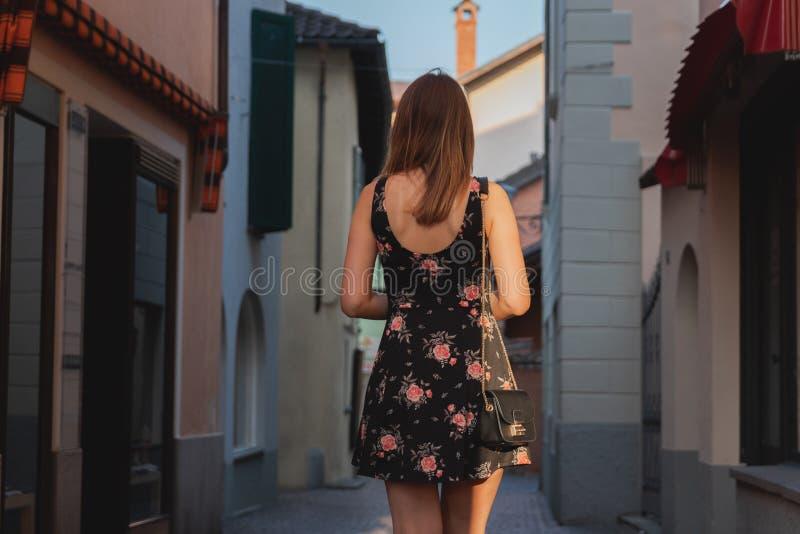 Jonge vrouw die winkelvenster bekijken in een steeg in ascona stock foto