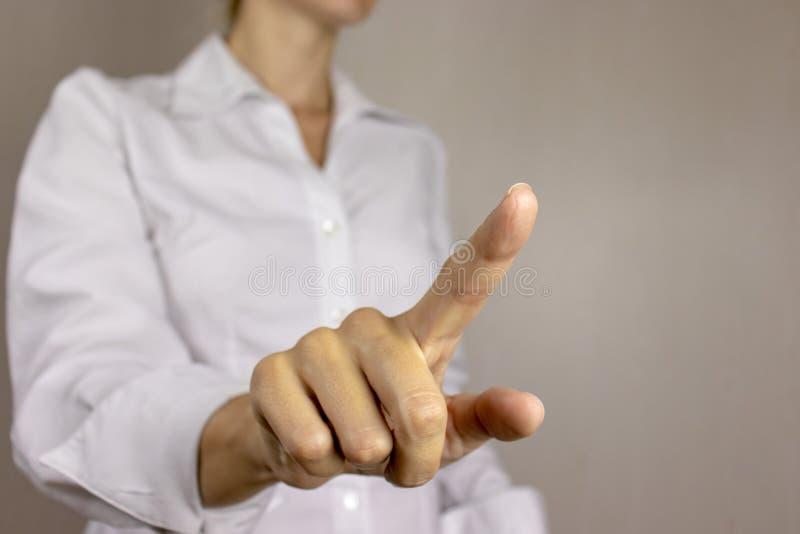 Jonge vrouw die in wit overhemd, duwende virtuele knoop met haar vinger richten Bedrijfs concept royalty-vrije stock fotografie