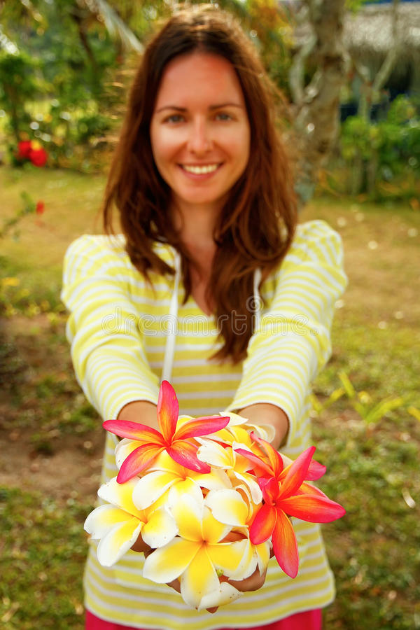 Jonge vrouw die witte en roze plumeriabloemen houden royalty-vrije stock foto's