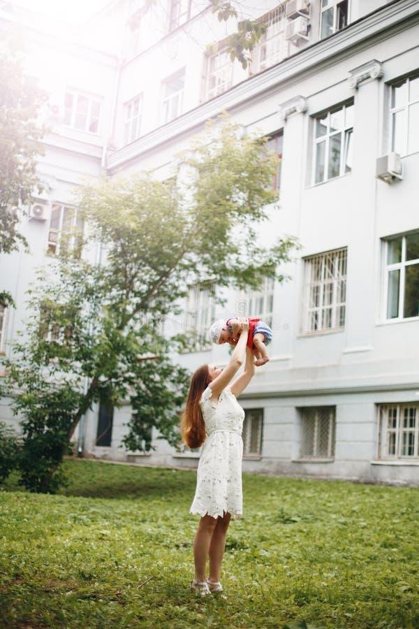 Jonge Vrouw die in Witte Kleding Haar Baby houden stock afbeeldingen