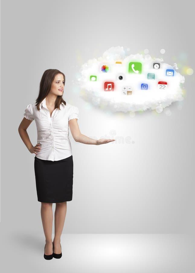 Jonge vrouw die wolk met kleurrijke app pictogrammen en symbolen voorstellen royalty-vrije stock foto