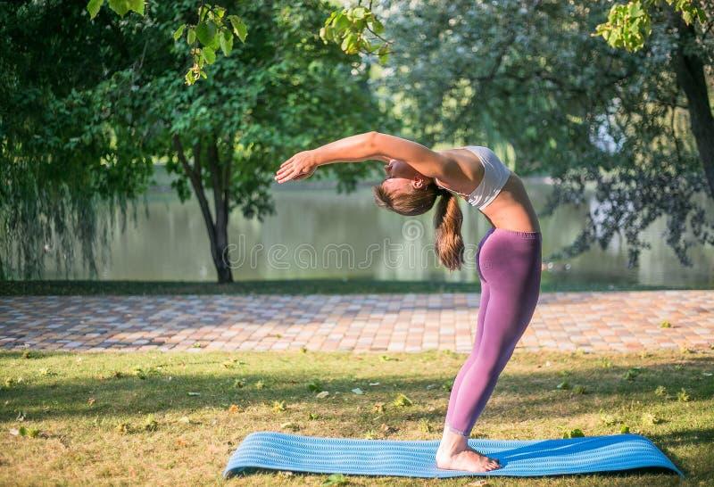 Jonge vrouw die yoga asan in Park dichtbij meer doen royalty-vrije stock afbeelding