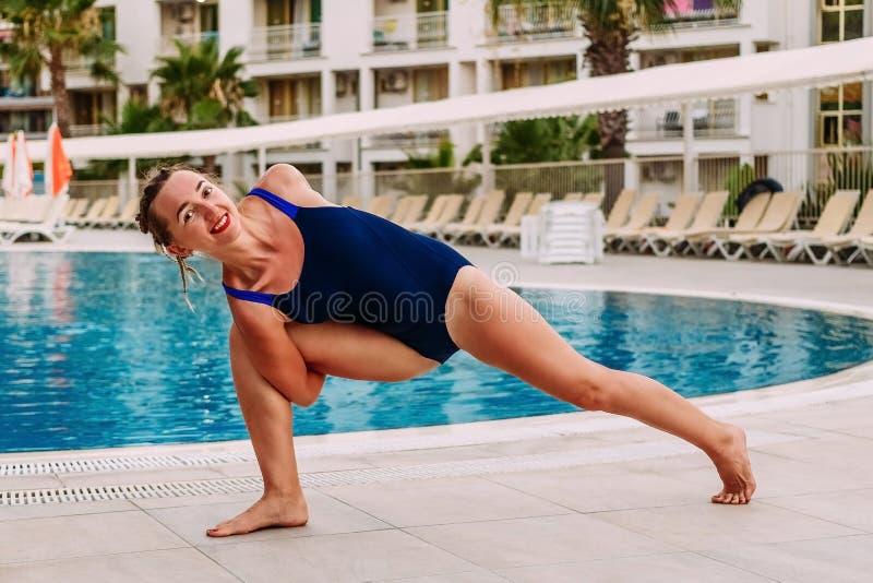 Jonge vrouw die yoga doen door de pool stock foto
