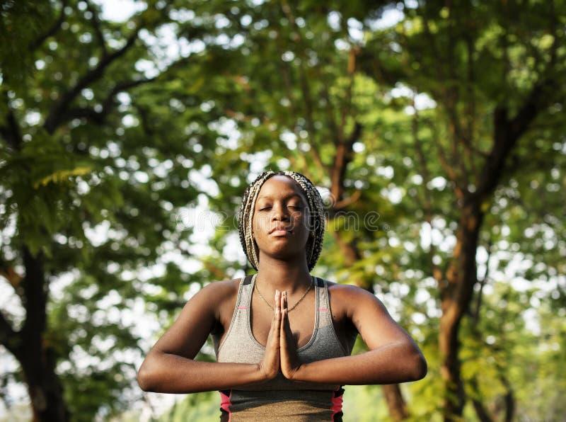 Jonge vrouw die yoga in het park doen stock fotografie
