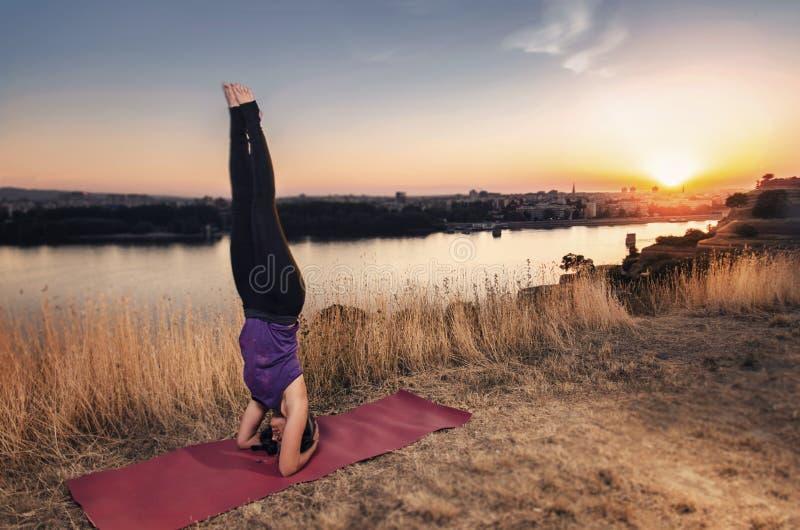 Jonge vrouw die yoga hoofdtribune doen bij zonsondergang royalty-vrije stock foto