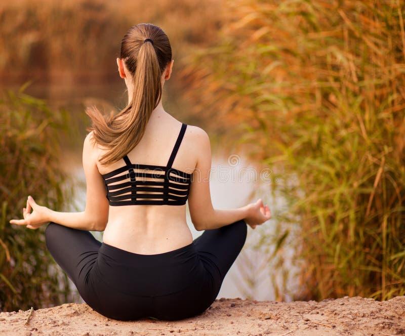 Jonge vrouw die yoga in ochtendpark doen Gezonde Levensstijl royalty-vrije stock foto