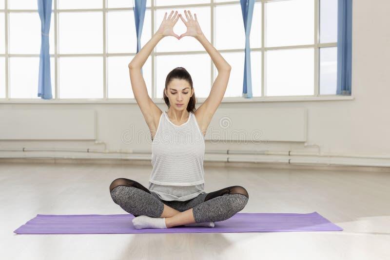 Jonge vrouw die yoga op de deken in de zaal doen royalty-vrije stock foto