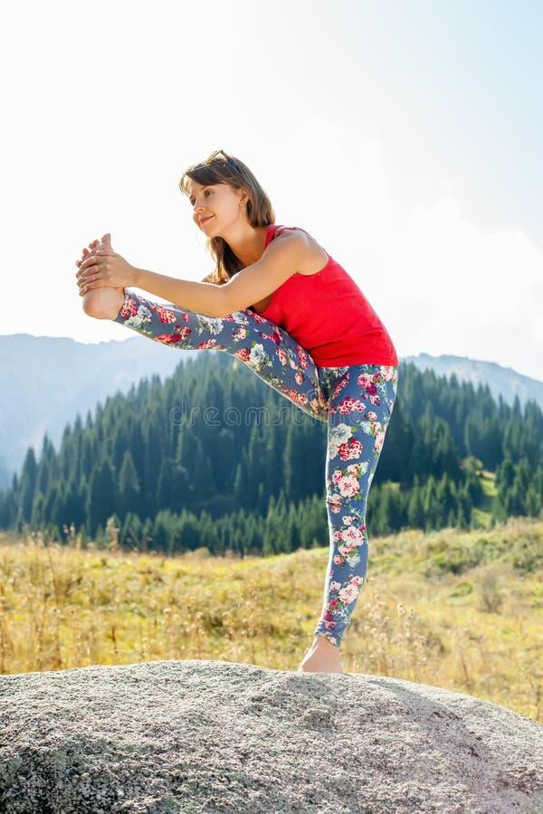 Jonge vrouw die yoga op een rots doen stock afbeeldingen
