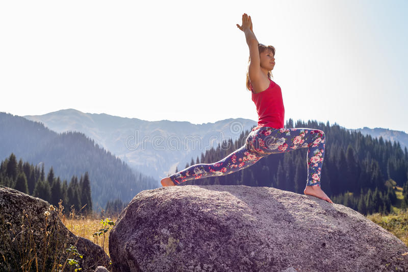 Jonge vrouw die yoga op een rots doen stock foto