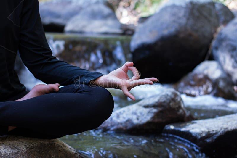 Jonge vrouw die yoga op rots doen royalty-vrije stock foto