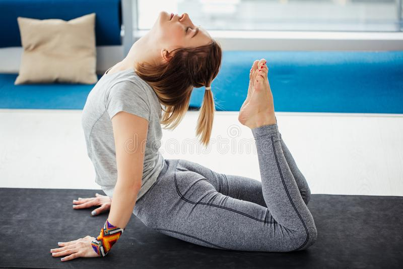 Jonge vrouw die yoga of pilates oefening doen De boog stelt met steun op handen stock foto