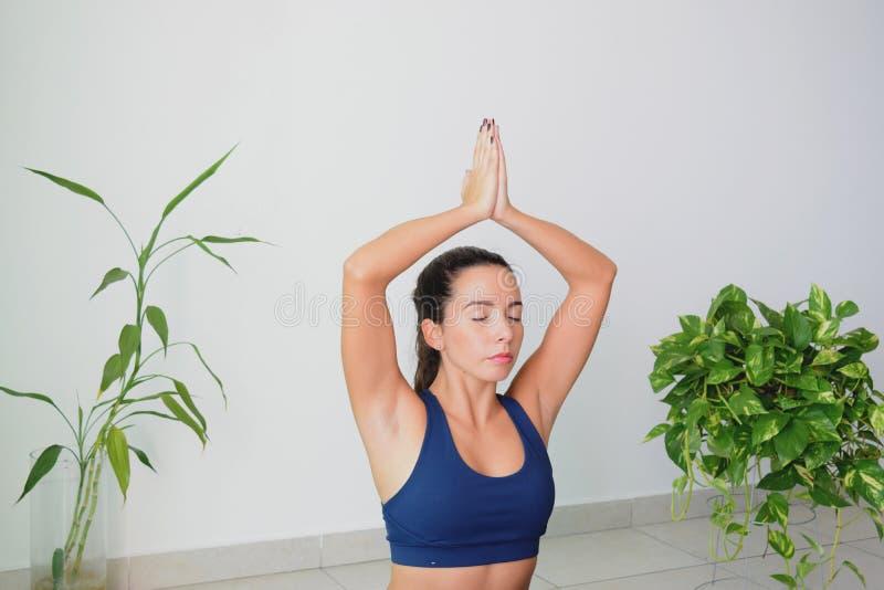 Jonge Vrouw die Yoga thuis doen stock afbeelding
