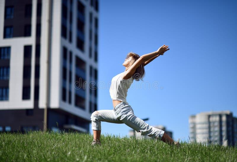 Jonge vrouw die yoga uitrekkende oefeningen doen bij het moderne stadspark royalty-vrije stock fotografie