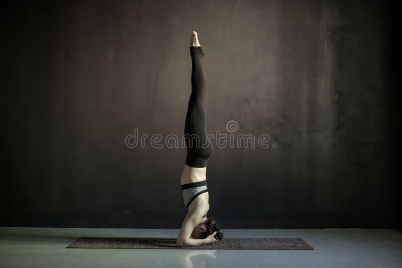 Jonge vrouw die yoga uitwerken die salambasirsasana doen stock foto's