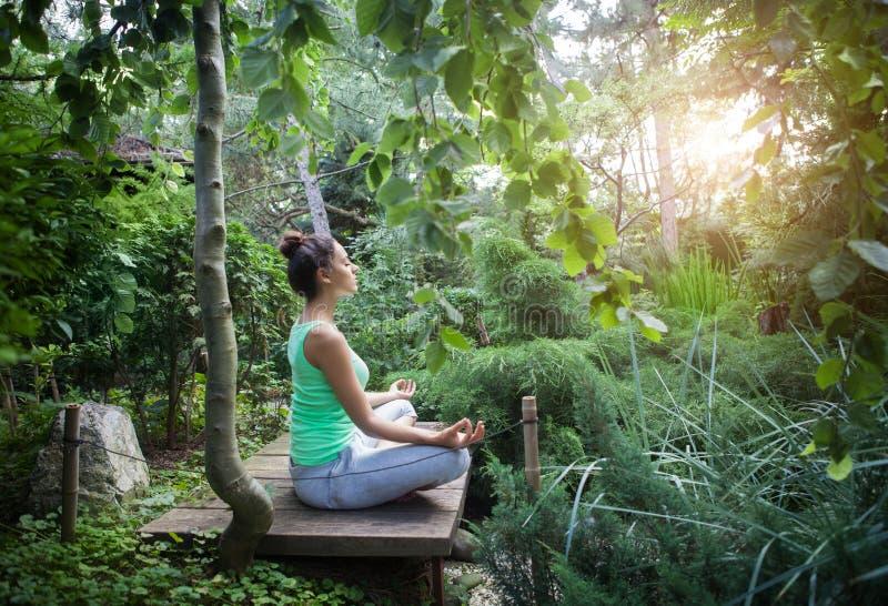 Jonge vrouw die yogaasana in de avond doen royalty-vrije stock foto