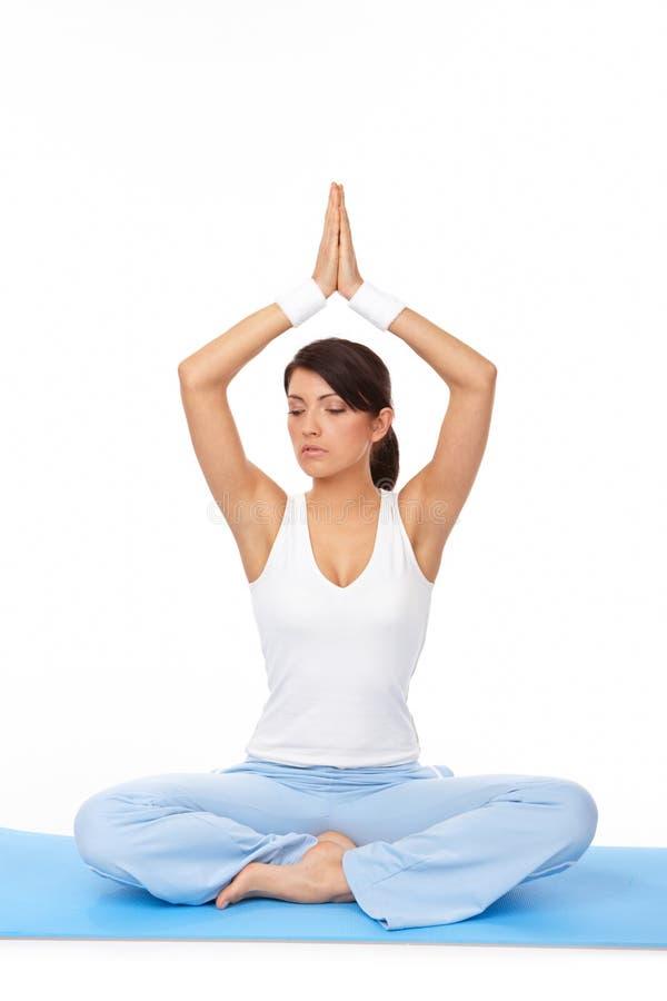 Jonge vrouw die yogaoefening op mat doet
