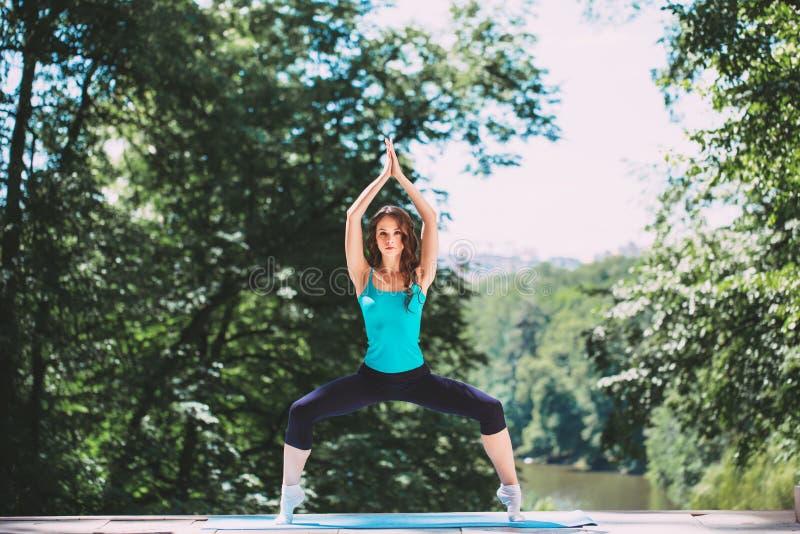 Jonge vrouw die yogaoefening in park doen stock foto's