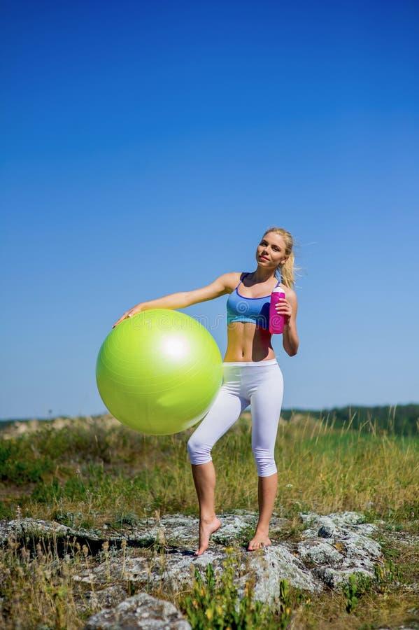 Jonge vrouw die yogaoefeningen op de bal doen stock fotografie