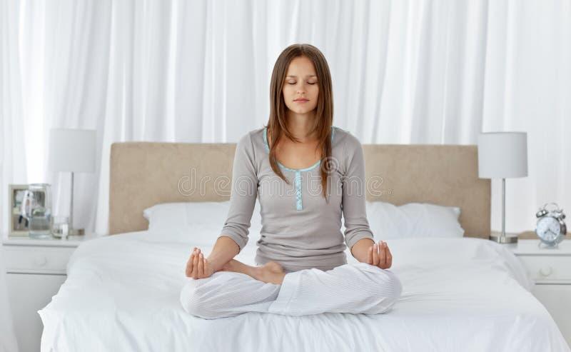 Jonge vrouw die yogaoefeningen op het bed doet royalty-vrije stock afbeelding
