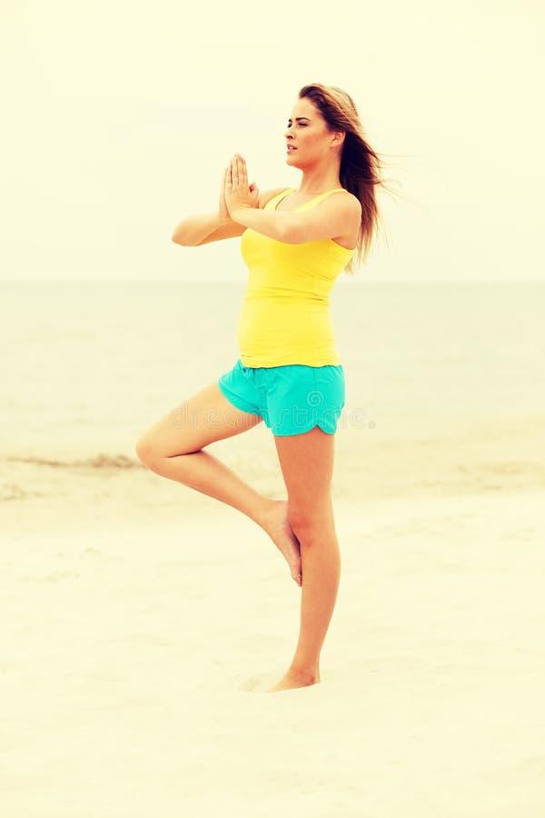 Jonge vrouw die yogaoefeningen op het strand maken stock foto's