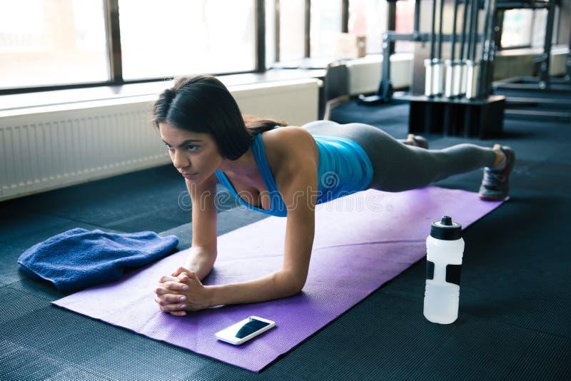 Jonge vrouw die yogaoefeningen op yogamat doen stock foto