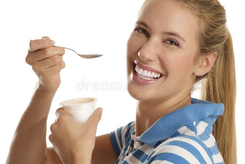 Jonge vrouw die yoghurt eet royalty-vrije stock afbeeldingen